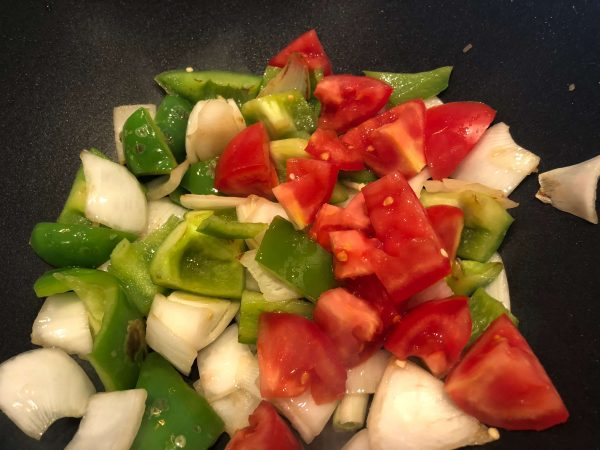 Gather the vegetables for the dish, and chop roughly into the same size - peppers, onions, tomatoes