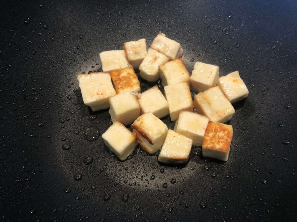 Add the tablespoon of oil to the kadai, and toast the paneer pieces until they start to brown. Do this quickly, and remove to a plate, saving the oil in the pan. Overcooking the paneer will make them tough