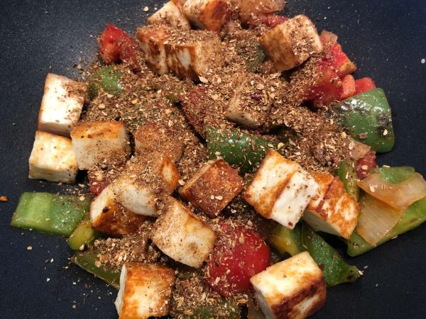 Add the paneer, and the powdered spices, and toss them around gently until the spice mix coats all the vegetables